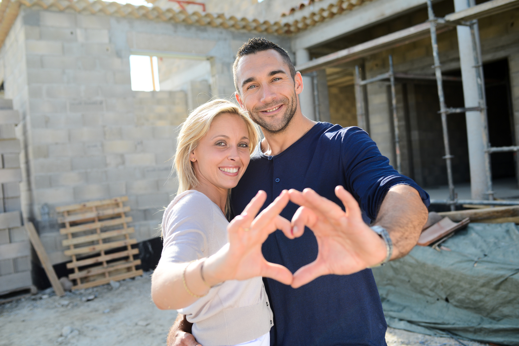 cheerful young happy couple in love in front of contruction site of new house